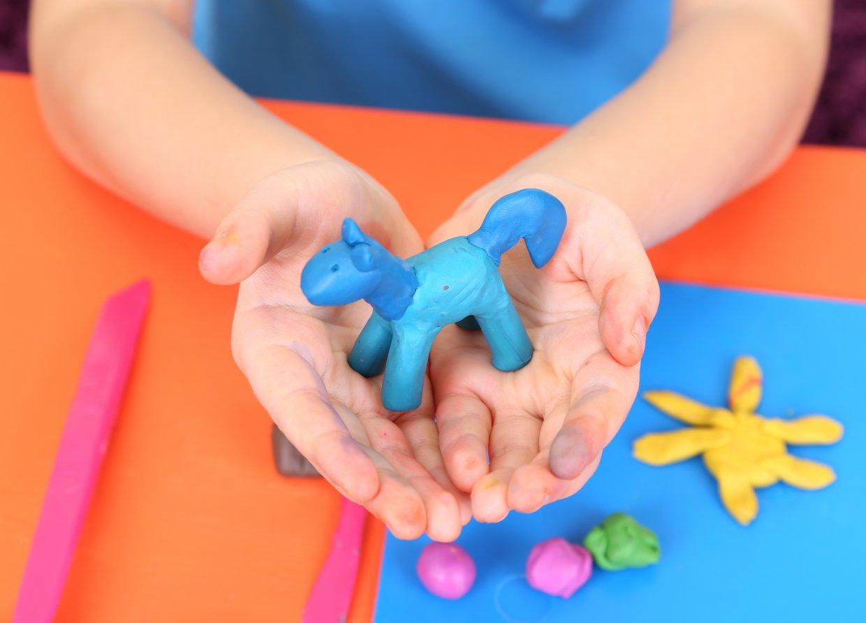 Child's,Hands,Holding,Hand Made,Plasticine,Hourse,Over,Desk